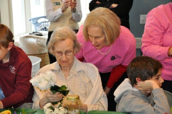 A Garden Club member helps a resident with her arrangement