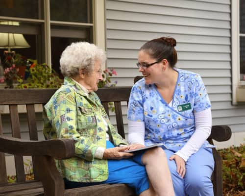 A resident and aide spending time in the courtyard